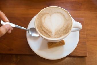 Chávena de café de cerâmica branca quente com arte de latte de forma de coração em madeira
