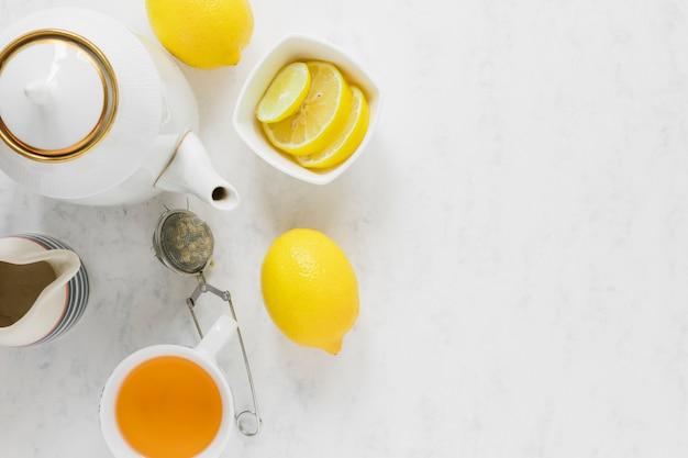 Chávena de chá de limão e chaleira com espaço de cópia
