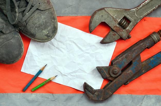 Chaves ajustáveis com botas velhas e uma folha de papel com dois lápis