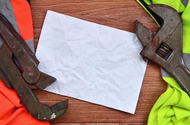Chaves ajustáveis e mentiras de papel de camisas de um trabalhador do sinal da laranja e do verde