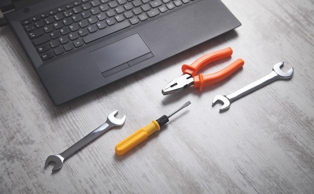 Chaves, alicates e chave de fenda com laptop. serviço de ti. apoio, suporte