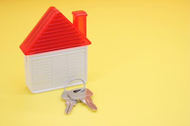 Chaves da casa e uma casa de brinquedo. o conceito de compra de imóveis. copie o espaço.