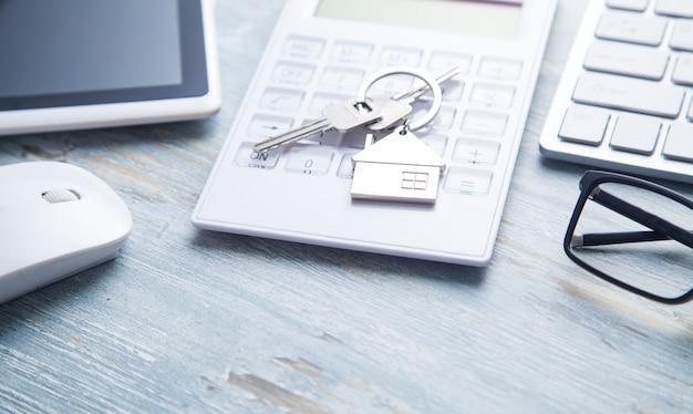 Chaves da casa na calculadora com objetos de negócios.