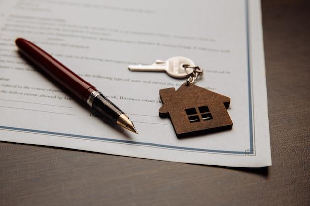 Chaves de casa e dinheiro em um contrato assinado de venda de casa