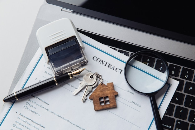 Chaves de casa, lupa e contrato