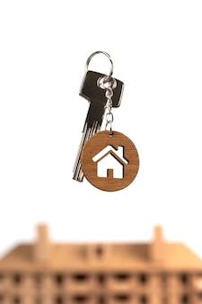 Chaves de conceito imobiliário com chaveiro em forma de casa contra modelo de casa marrom
