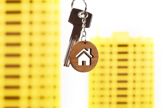 Chaves de conceito imobiliário com chaveiro em forma de casa contra modelos de casas amarelas brilhantes