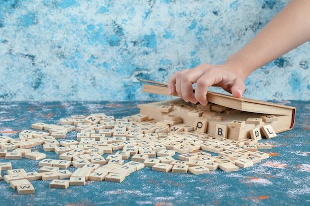 Chaves de dominó de madeira com letras impressas em uma caixa de madeira