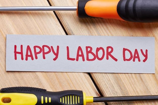 Chaves de fenda e cartão do dia do trabalho. papel de felicitações na prancha de madeira. festival para os trabalhadores.