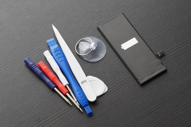 Chaves de fenda, pinças e uma nova bateria de smartphone em uma mesa de madeira.