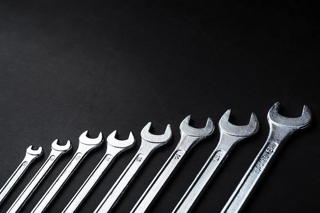 Chaves de ferramenta em uma linha em um fundo preto com espaço livre.