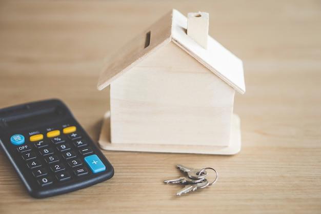 Chaves de modelo de casa e calculadora na mesa