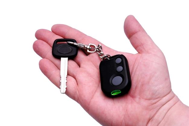 Chaves do automóvel e painel de controle remoto do sistema de alarme do carro em uma mão.