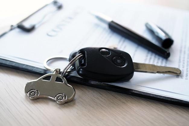 Chaves do carro colocadas em documentos do contrato sobre empréstimos de carro.