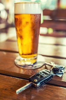 Chaves do carro e um copo de cerveja ou álcool destilado na mesa de um bar ou restaurante.