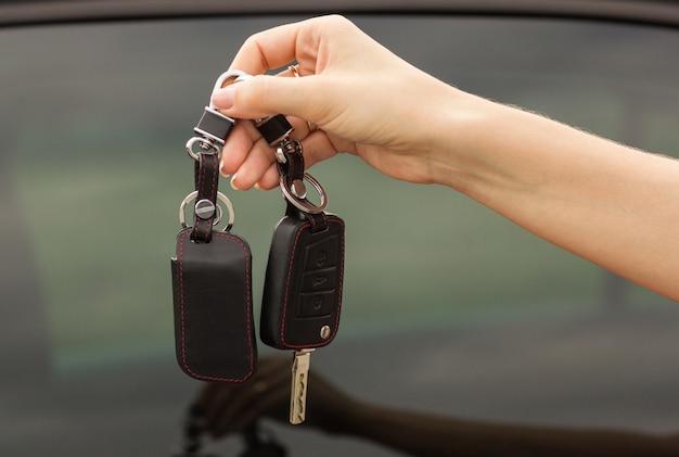 Chaves do carro em uma mão feminina, close-up