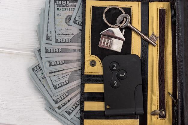 Chaves do carro homa nad com notas de dólar na mesa. conceito de economia