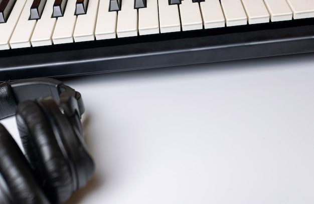 Chaves do piano e fones de ouvido com o espaço da cópia, isolado. teclado sintetizador