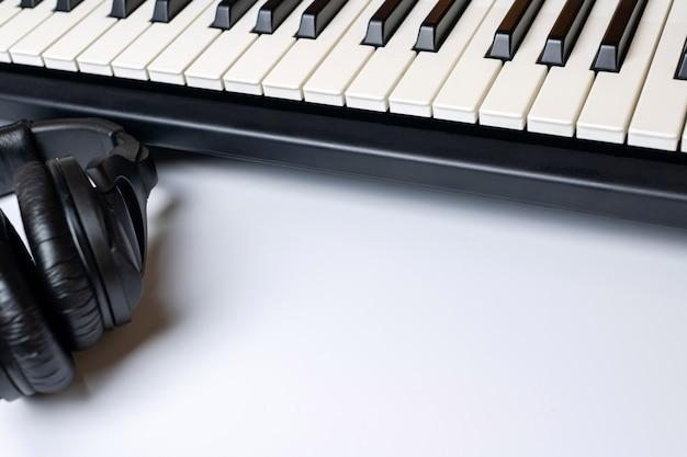 Chaves do piano e fones de ouvido com o espaço da cópia, isolado.