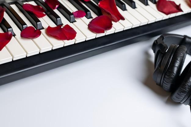 Chaves do piano espalhadas com as pétalas cor-de-rosa e os fones de ouvido vermelhos, isolados, espaço da cópia.
