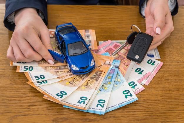 Chaves e carro de brinquedo em dinheiro do euro, mãos femininas