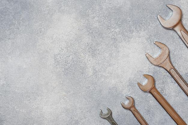 Chaves, ferramentas no fundo concreto cinzento com espaço da cópia.