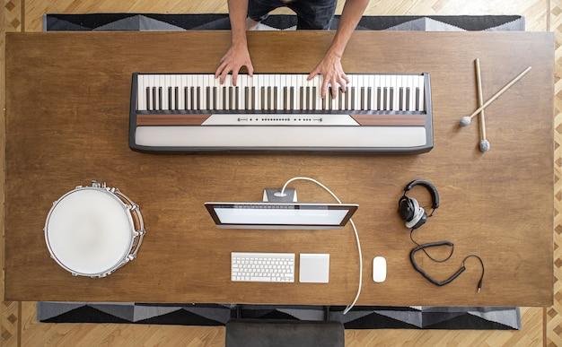 Chaves musicais, baquetas, bateria, fones de ouvido e um computador em uma mesa de madeira. local de trabalho de um músico para trabalhar o som.