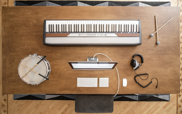Chaves musicais, baquetas, bateria, fones de ouvido e um computador em uma mesa de madeira.