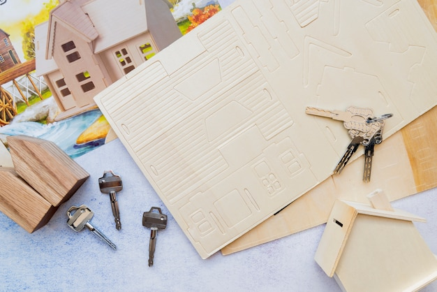Chaves sobre a casa de papel cartão com modelo de casa de madeira