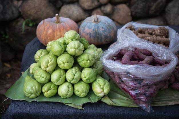 Chayote, batata doce, abóbora e gengibre frescos no mercado vegetal da tenda.