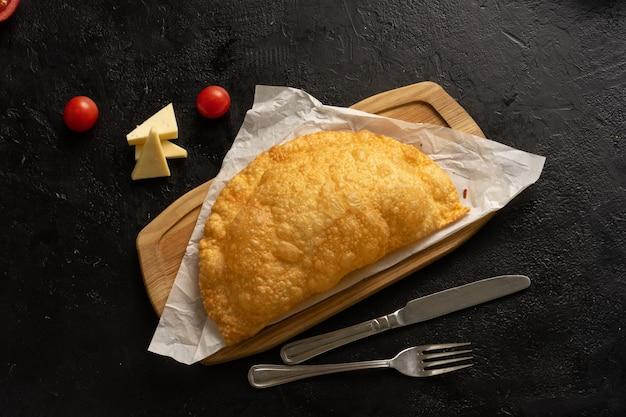 Cheburek com carne, queijo e tomate em uma placa de madeira ao lado de talheres e ingredientes em uma mesa preta. vista do topo.