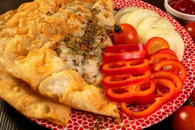 Cheburek de torta picante com carne, polvilhada com especiarias, com tomate, pimentão e ketchup.