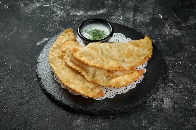 Chebureki é uma receita frita com recheio de carne moída ou picada e cebola em um prato de ardósia preta sobre mesa escura. chebureki é o prato da culinária tártara da crimeia