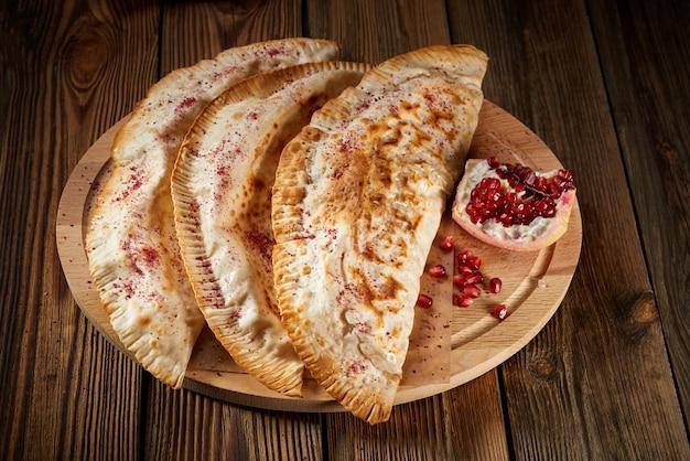 Chebureki frito com carne em uma mesa de madeira com romã