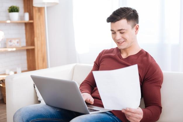 Checagem final. aluno alegre e alegre carregando papel enquanto usa o laptop