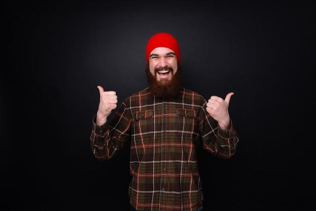 Cheeful barbudo com chapéu vermelho mostrando os polegares para cima sobre um fundo escuro isolado