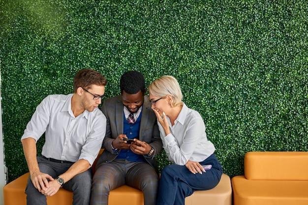 Cheeful colegas sentam-se juntos no corredor, tendo momentos de lazer, olhando para a tela do celular sorrindo