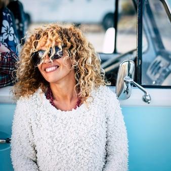 Cheeful e linda loira encaracolada jovem adulta caucasiana sorrindo e rindo com óculos escuros e uma van vintage azul na cena