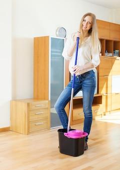 Cheeful mulher comum lavando parquet com esfregão