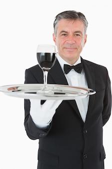 Cheerful garçom segurando um copo de vinho em uma bandeja de prata