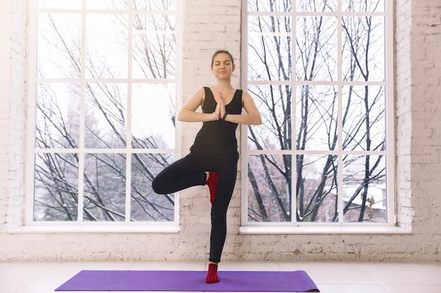 Cheerfull jovem fazendo ioga sozinha no estúdio de ioga perto da janela de manhã