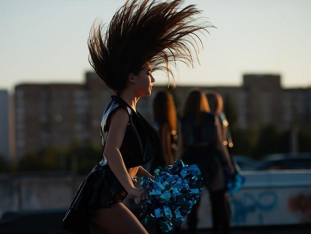 Cheerleaders dançando no telhado ao pôr do sol contra a paisagem da cidade