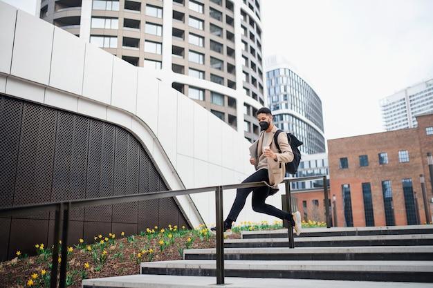 Cheerul homem com laptop se divertindo no caminho para trabalhar ao ar livre na cidade, o conceito de coronavírus.