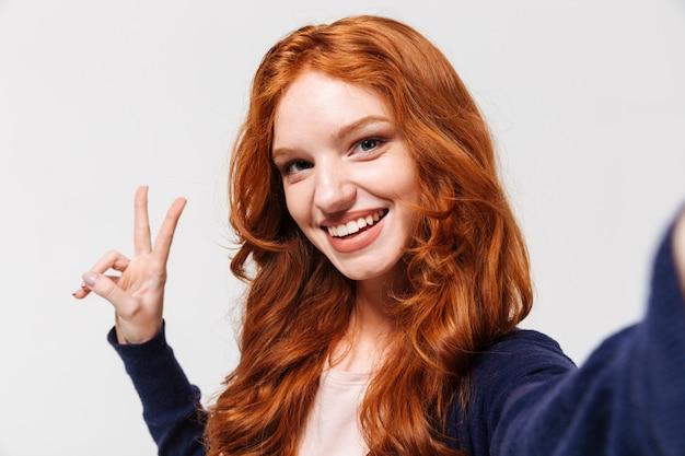 Cheerul jovem ruiva senhora fazer selfie