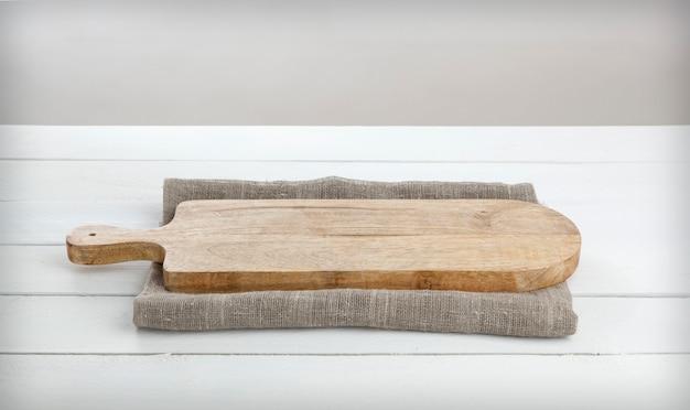 Cheeseboard vazio na mesa de madeira branca.