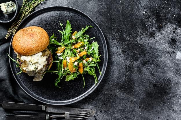 Cheeseburger caseiro com queijo azul, bacon, marmelada de carne e cebola marmoreada, um prato de salada com rúcula e laranjas. fundo preto. vista do topo. copie o espaço