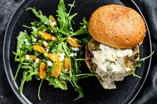Cheeseburger caseiro com queijo azul, bacon, marmelada de carne e cebola marmoreada, um prato de salada com rúcula e laranjas. fundo preto. vista do topo