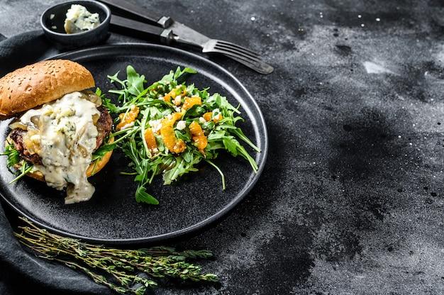 Cheeseburger caseiro com queijo azul, bacon, marmelada de carne e cebola marmoreada, um prato de salada com rúcula e laranjas. superfície preta. vista do topo. copie o espaço