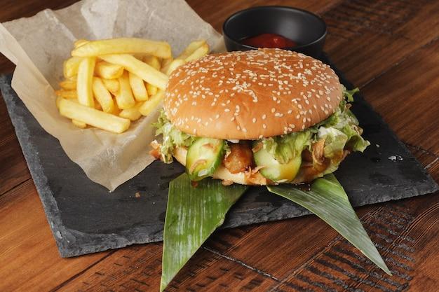 Cheeseburger com batatas fritas e molho em um fundo de madeira marrom