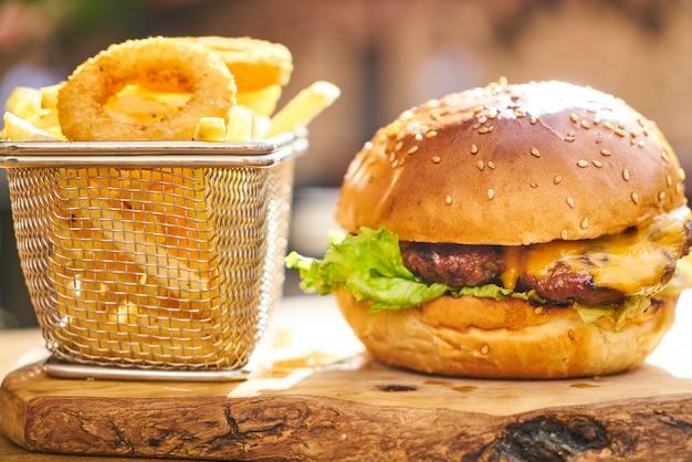 Cheeseburger com batatas fritas na mesa de madeira
